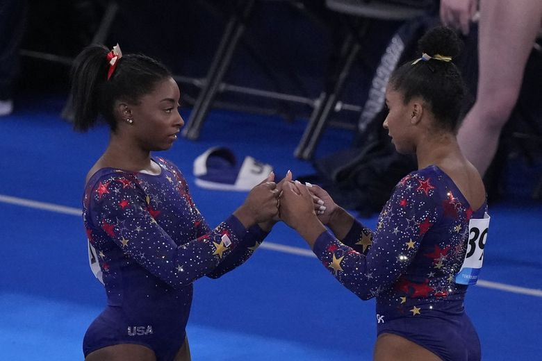 Jordan Chiles, right, of the United States, and teammate Simone Biles, fist bump each other before their floor exercise performance on Sunday. Chiles is from Vancouver, Washington. (Gregory Bull / The Associated Press)