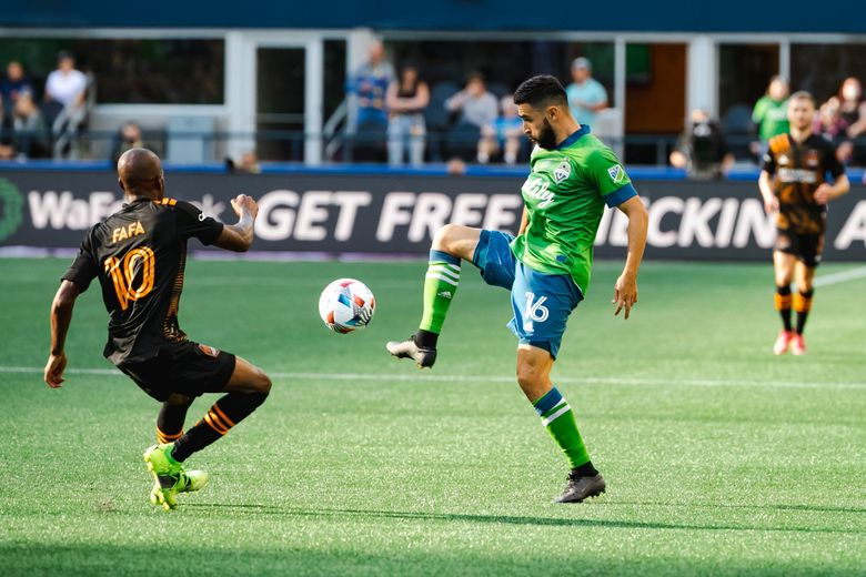 Houston's Fafa Picault defends Seattle's Alex Roldan during the Houston Dynamo FC versus Seattle Sounders FC in Major League Soccer game Wednesday, July 7, 2021 at Lumen Field in Seattle, Wash. (Erika Schultz / The Seattle Times)