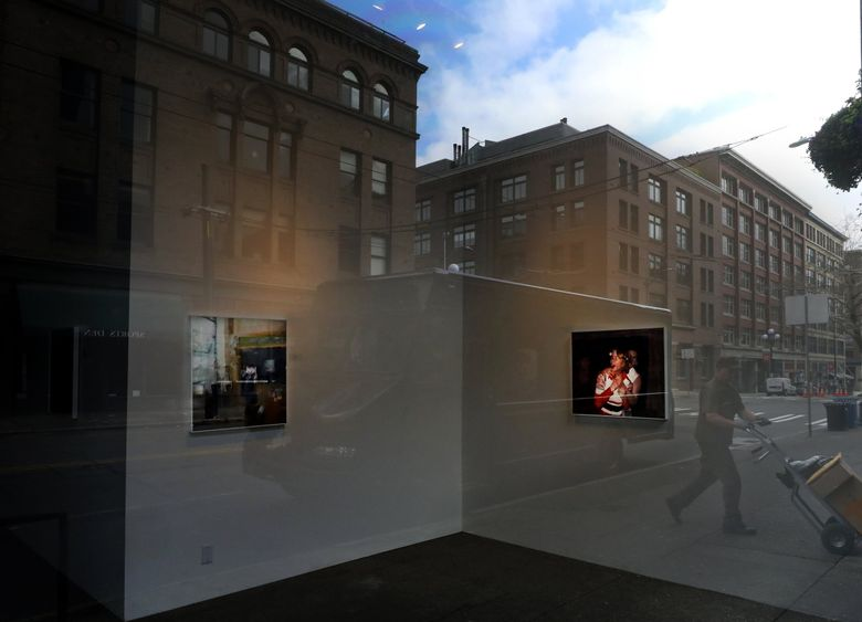 Pioneer Square is reflected in the window of Linda Hodges Gallery in Pioneer Square on April 1, 2020, when the First Thursday art walk was canceled because of the coronavirus pandemic. First Thursday is finally coming back on Aug. 5. (Alan Berner / The Seattle Times)