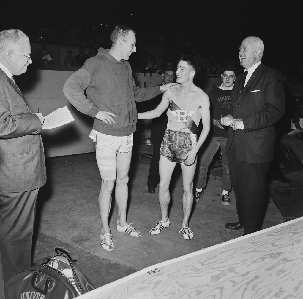 Phil Shinnick of Washington, left, his leg taped, congratulates Spokane's Gerry Lindgren on winning the two-mile event in the San Francisco Holiday Invitational track meet on Dec. 28, 1963. Shinnick won the broad jump with a leap of 25-feet 6½ inches. Lindgren, of Rogers High School, carded 9 minutes flat for the two-mile. (Robert W. Klein / AP)