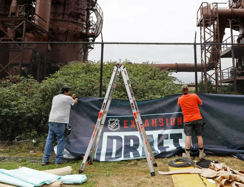 Workers put up banners on a fence as part of the preparations Tuesday July, 20, 2021 in Seattle's Gas Works Park for Wednesday's Kraken NHL Expansion Draft. (Ken Lambert / The Seattle Times)