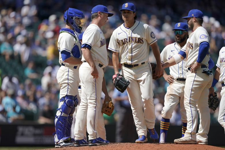 Mariners pitcher Marco Gonzales, center, walks off the mound after he was pulled by manager Scott Servais, second from left, during the sixth inning Sunday. (Ted S. Warren / The Associated Press)