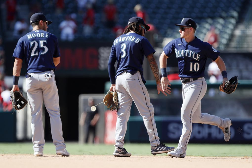 Seattle Mariners' Dylan Moore, left, J.P. Crawford and Jarred Kelenic, right, celebrate the team's 7-4 win in a baseball game against the Los Angeles Angels in Anaheim, Calif., Sunday, July 18, 2021.  (Alex Gallardo / The Associated Press)