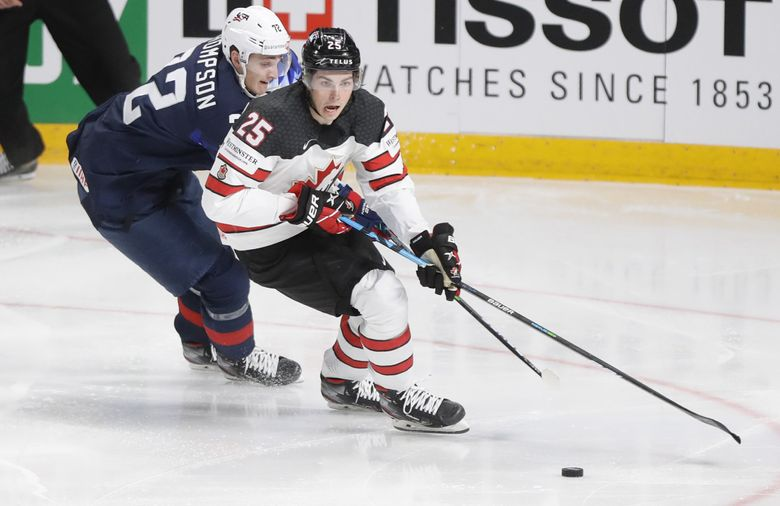 Canada's Owen Power, right, challenges for the puck with Tage Thompson of the US during the Ice Hockey World Championship semifinal match between the United States and Canada at the Arena in Riga, Latvia, on June 5, 2021. (AP Photo/Sergei Grits) (