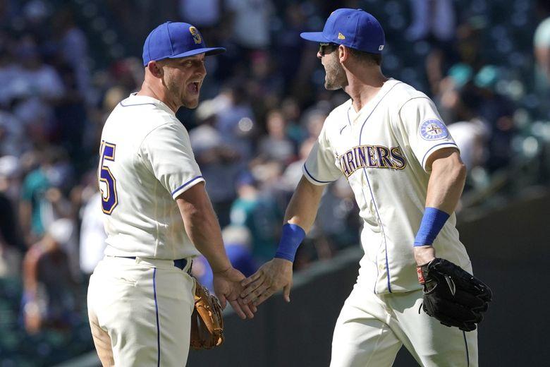 Seattle Mariners' Kyle Seager, left, is greeted by Mitch Haniger, right, after they defeated the Oakland Athletics in a baseball game, Sunday, July 25, 2021, in Seattle. (Ted S. Warren / The Associated Press)