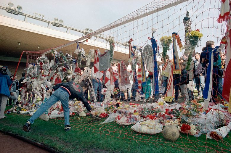 FiLE – In this file photo dated April 16, 1989, a Liverpool Football Club fan places a pair of football boots in the goal at the Kop end of Anfield Stadium as hundreds came to mourn the loss of fellow Liverpool fans.  Liverpool players and staff have observed 97 seconds of silence in honor of Andrew Devine. The lifelong fan died Tuesday, July 27, 2021 from long-term injuries sustained in the Hillsborough disaster. He was 55.  (AP Photo/Peter Kemp, File)
