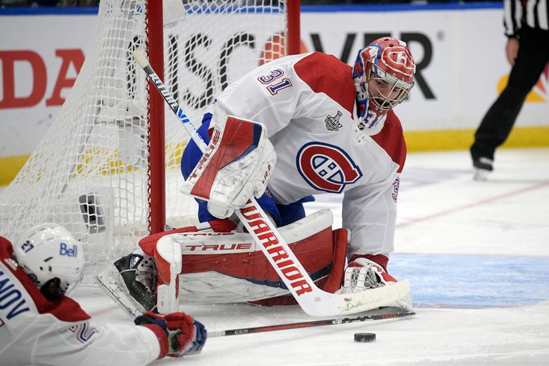 Montreal Canadiens goaltender Carey Price (31) plays the puck during the first period in Game 5 of the NHL hockey Stanley Cup Final against the Tampa Bay Lightning, Wednesday, July 7, 2021, in Tampa, Fla. (AP Photo/Phelan Ebenhack)