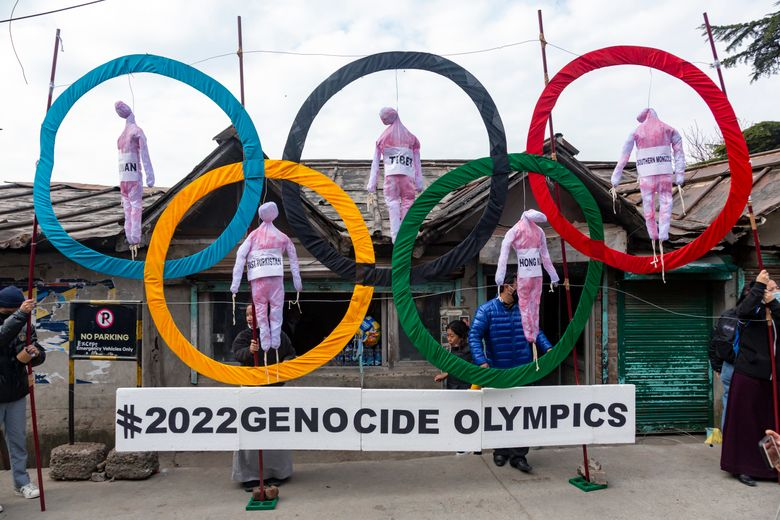 """FILE – In this Feb. 3, 2021, file photo, exile Tibetans use the Olympic rings as a prop as they hold a protest against the holding of the 2022 Beijing Winter Olympics, in Dharmsala, India. Facing the boycott-threatened Beijing Winter Olympics in just over six months, the International Olympic Committee said on Wednesday, July 28, that its only responsibility was to """"deliver the Games"""" and not to monitor human rights. (AP Photo/Ashwini Bhatia, File)"""