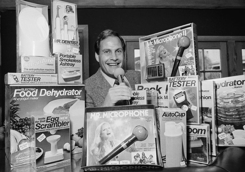 In this photo from Dec. 8, 1982, Ron Popeil, the man behind those late-night, rapid-fire television commercials that sell everything from the Mr. Microphone to the Pocket Fisherman to the classic Veg-a-Matic, sits surrounded by his wares in his office in Beverly Hills, Calif.  Ron Popeil, the quintessential TV pitchman and inventor known to generations of viewers for hawking products including the Veg-O-Matic, the Chop-O-Matic, Mr. Microphone and the Showtime Rotisserie and BBQ, died Wednesday, July 28, 2021 his family said. (AP Photo/Reed Saxon, File)