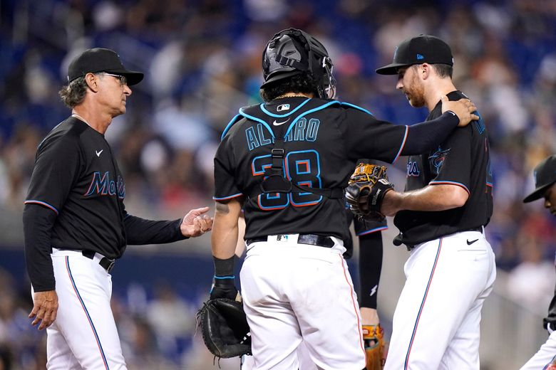 Miami Marlins manager Don Mattingly, left goes to the mound to remove starting pitcher Zach Thompson, right, during the sixth inning of the team's baseball game against the New York Yankees, Friday, July 30, 2021, in Miami. At center is catcher Jorge Alfaro (38). (AP Photo/Lynne Sladky)