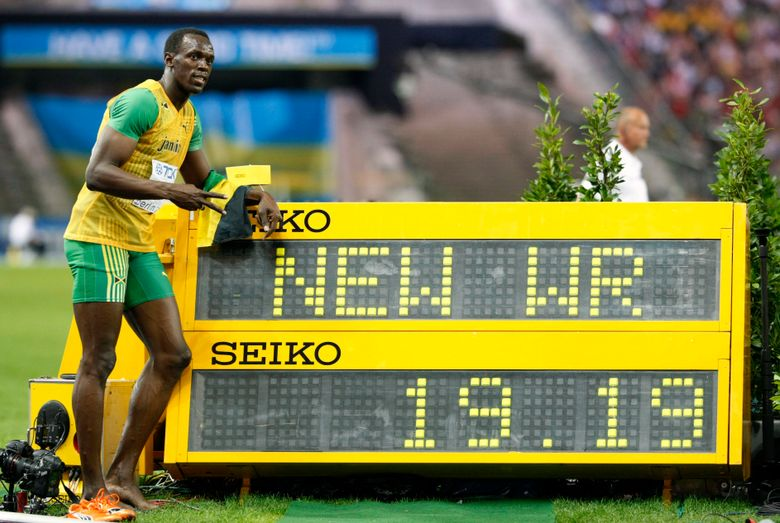 FILE – In this Aug. 20, 2009, file photo, Jamaica's Usain Bolt poses beside the timing board showing the new World Record after he won the Men's 200-meter final during the World Athletics Championships in Berlin. (AP Photo/Anja Niedringhaus, File)