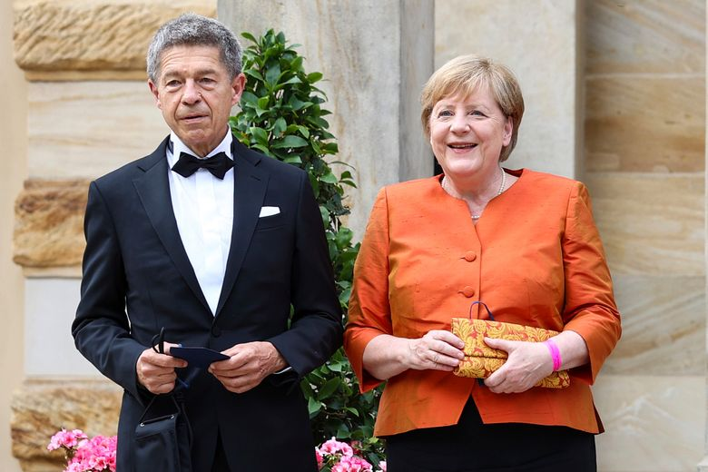 """German Chancellor Angela Merkel and her husband Joachim Sauer arrives at Festival Hall in Bayreuth, Germany, Sunday July 25, 2021, at the start of the Richard Wagner Festival with a new production of the opera """"The Flying Dutchman"""".  (Daniel Karmann/dpa via AP)"""
