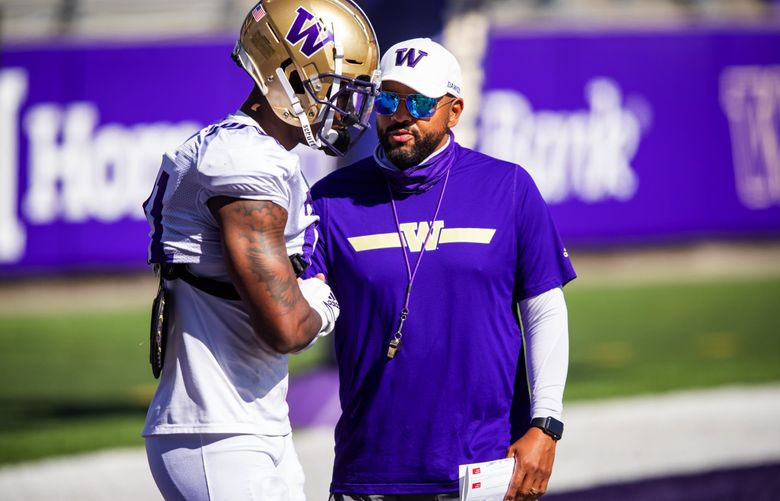 Huskies defensive back Dominique Hampton shakes hands with head coach Jimmy Lake as the University of Washington Huskies participate in spring practice at Husky Stadium Saturday April 17, 2021 in Seattle. (Bettina Hansen / The Seattle Times)