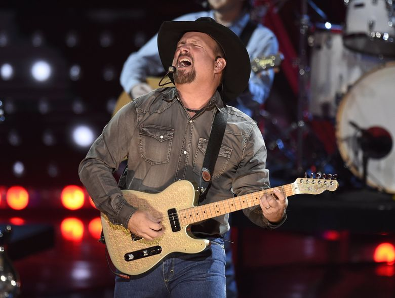Country star Garth Brooks, shown  here performing at the iHeartRadio Music Awards in Los Angeles in 2019, had set a Sept. 4 date in Seattle as part of his Stadium Tour. On Tuesday, the tour said it was halting Seattle ticket sales due to uncertainty surrounding the coronavirus pandemic resurgence. (Chris Pizzello / Invision / AP)