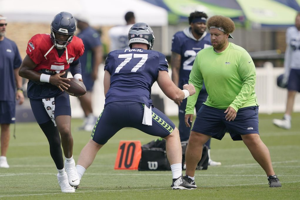 Seattle Seahawks backup quarterback Geno Smith, left, takes a snap from center Ethan Pocic (77) as run game coordinator Andy Dickerson, right, helps with a drill Tuesday, Aug. 3, 2021, in Renton, Wash. (Ted S. Warren / The Associated Press)