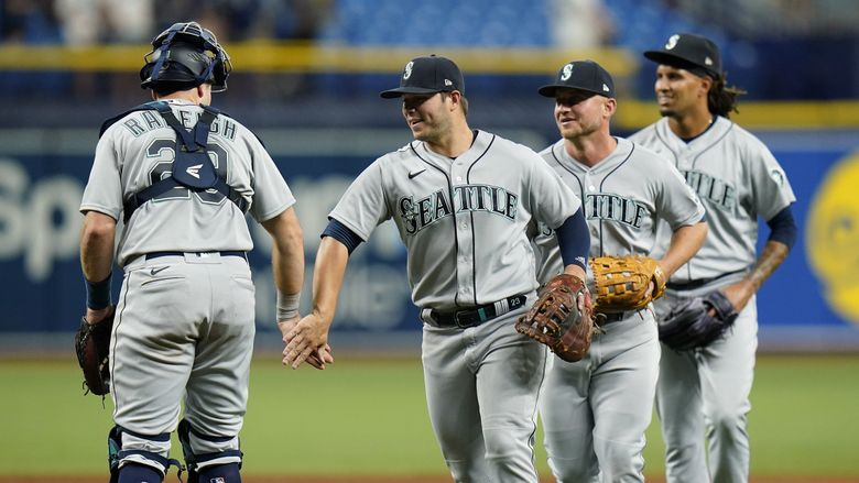 Seattle Mariners' Ty France, second from left, celebrates with teammates, including Cal Raleigh (29) after the Mariners defeated the Tampa Bay Rays during a baseball game Monday, Aug. 2, 2021, in St. Petersburg, Fla. (Chris O'Meara / The Associated Press)