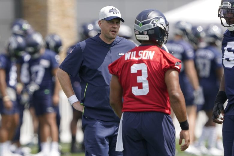 Seahawks offensive coordinator Shane Waldron, left, talks with quarterback Russell Wilson (3) during practice, Wednesday, July 28, 2021, in Renton. (Ted S. Warren / The Associated Press)