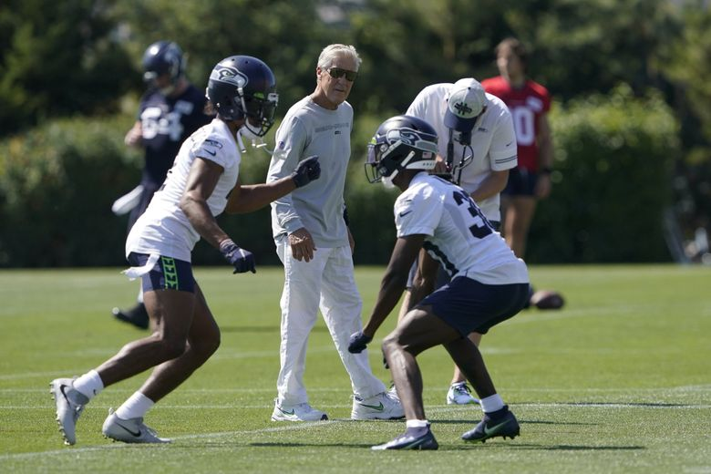 Seattle Seahawks head coach Pete Carroll, center, watches as cornerback Ahkello Witherspoon, left, runs a drill with cornerback Bryan Mills, right, during NFL football practice Thursday, July 29, 2021, in Renton, Wash. (Ted S. Warren / The Associated Press)