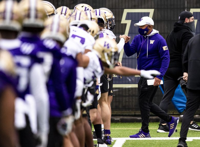 Head coach Jimmy Lake fist pumps a player while the team stretches during spring practice at the east practice field on Wednesday, April 7, 2021. (Amanda Snyder / The Seattle Times)