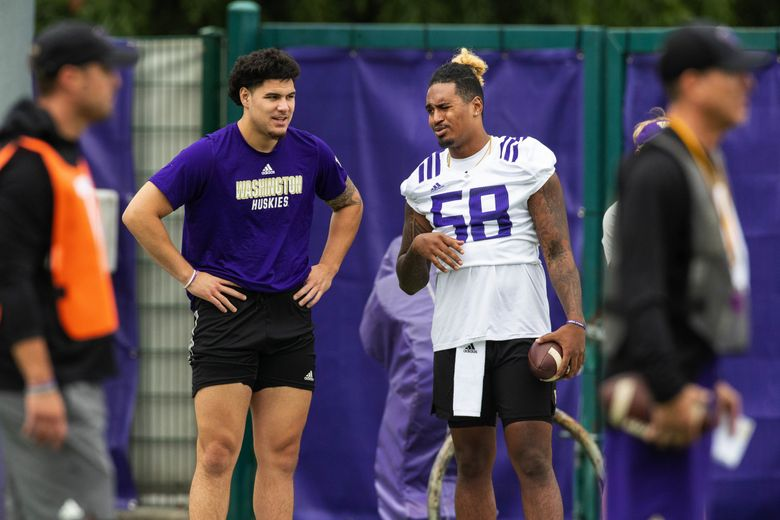 Laiatu Latu, left, medically retired due to injuries, but was present for Friday's first practice.  Also injured, but expected to return this season, was Zion Tupuola-Fetui, right. . The Washington Huskies opened fall camp Friday, August 6, 2021. 217829 (Dean Rutz / The Seattle Times)