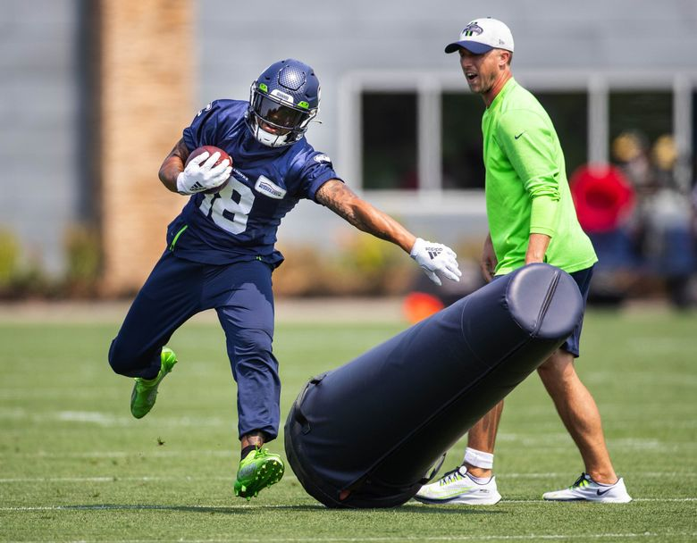 Wide receiver Freddie Swain runs through tackling dummies during drills Monday.  The Seattle Seahawks practiced Monday, August 2, 2021 at the VMAC in Renton, WA. (Dean Rutz / The Seattle Times)