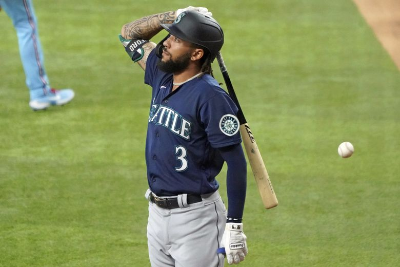 Seattle Mariners' J.P. Crawford heads back to the dugout after lining into a double play against the Texas Rangers in the second inning of a baseball game, Sunday, Aug. 1, 2021, in Arlington, Texas. (Louis DeLuca / The Associated Press)