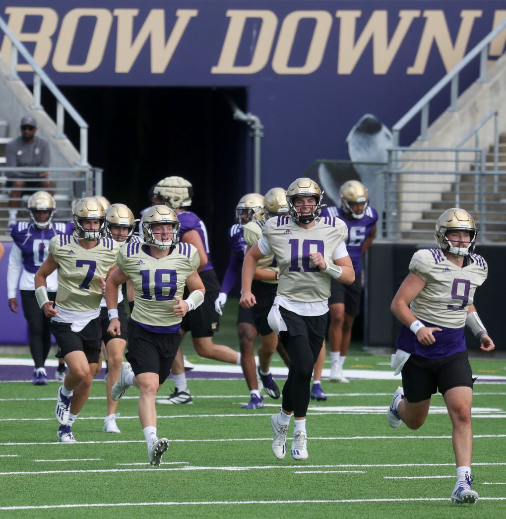 Quarterbacks from left, Sam Huard (7), Camden Sirmon (18), Patrick O'Brien (10) and Dylan Morris (9) break off to their own field for more drills during University of Washington football practice, Sunday, Aug. 8, 2021 in Seattle. This is UW football camp day 3. (Ken Lambert / The Seattle Times)