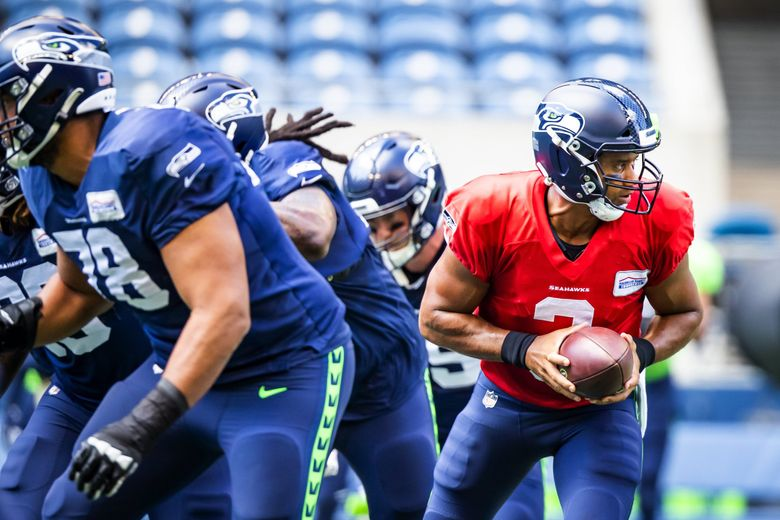 Seahawks quarterback Russell Wilson takes the hand-off in warmups before the Seahawks play a mock game as part of training camp at Lumen Field in Seattle Sunday, August 8, 2021. (Bettina Hansen / The Seattle Times)