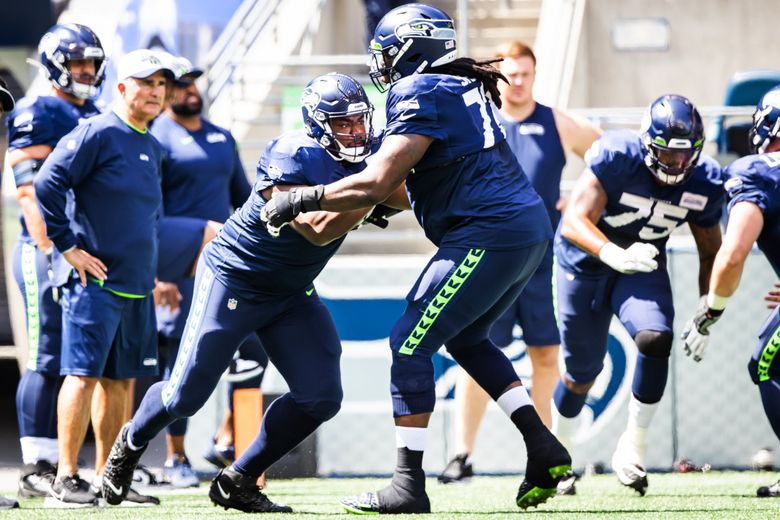 Seahawks offensive guard Phil Haynes, left, and offensive tackle Brandon Shell warm up before a mock game as part of training camp at Lumen Field in Seattle, Aug. 8, 2021. (Bettina Hansen / The Seattle Times)