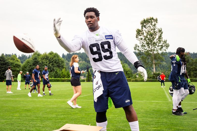 Seahawks defensive end Aldon Smith tosses a signed football to fans after Seahawks Training Camp at the Virginia Mason Athletic Center in Renton Saturday July 31, 2021. (Bettina Hansen / The Seattle Times)