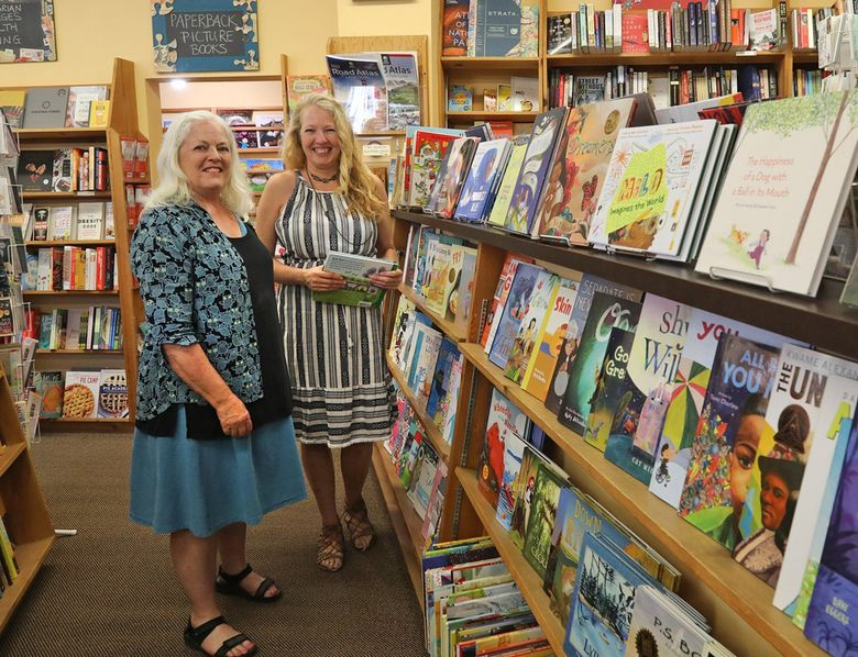 Edmonds Bookshop owner Mary Kay Sneeringer, left, and Michelle Bear, the store's asstistant manager, show off the colorful children's section at their independent bookstore Tuesday, Aug. 10, 2021. Sneeringer is selling the shop to Bear after owning the store for two decades. (Greg Gilbert / The Seattle Times)