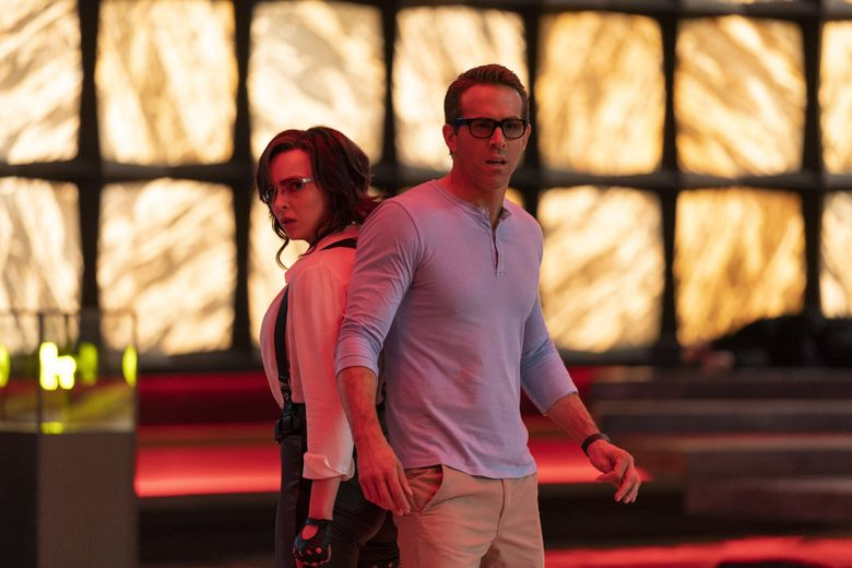 """This image released by 20th Century Studios shows Jodie Comer, left, as Millie/Molotovgirl opposite Ryan Reynolds as Guy in a scene from """"Free Guy."""" (Alan Markfield / 20th Century Studios via The Associated Press)"""