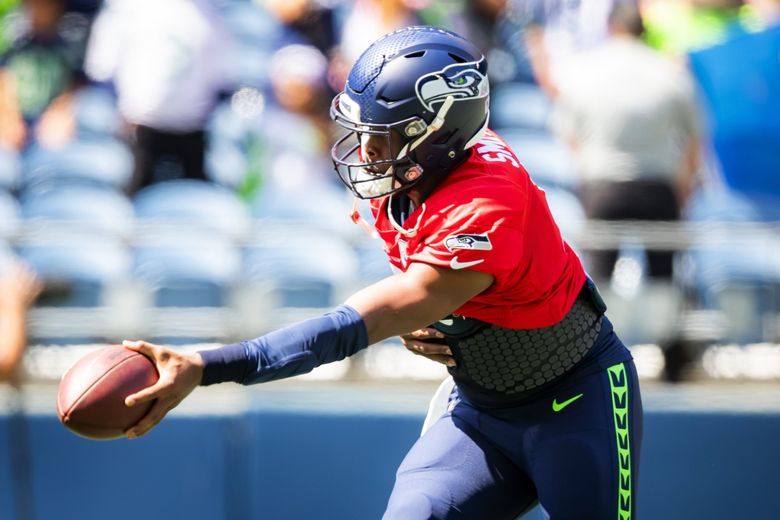 Seahawks backup quarterback Geno Smith practices a hand-off during warmups before a mock game at Lumen Field in Seattle on Aug. 8. (Bettina Hansen / The Seattle Times)