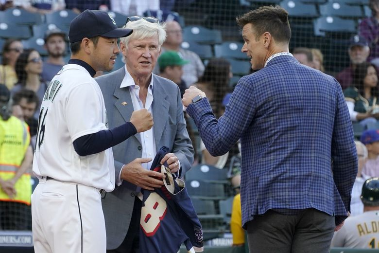 Seattle Mariners pitcher Yusei Kikuchi, left, greets general manager Jerry Dipoto, right, as Mariners owner John Stanton, center, prepares to present Kikuchi with his jersey from the MLB All-Star Game during a ceremony before a baseball game against the Oakland Athletics, July 22, 2021, in Seattle. (Ted S. Warren / AP)
