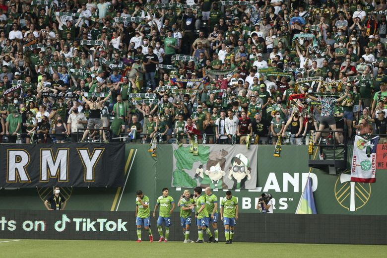 Seattle Sounders players celebrate a 1-0 lead over the Portland Timbers during the first half of an MLS match at Providence Park on Sunday, Aug. 15, 2021.(Sean Meagher / AP)