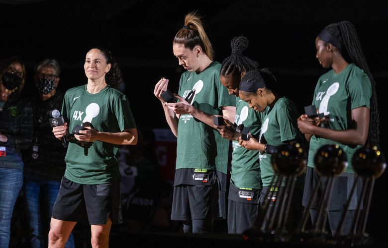 While Sue Bird addresses the crowd at Angel of the Winds Arena, her teammates look over their WNBA championship rings.  The Las Vegas Aces played the Seattle Storm in the season opener for both teams Saturday, May 15, 2021, at Angel of the Winds Arena in Everett, WA. (Dean Rutz / The Seattle Times)