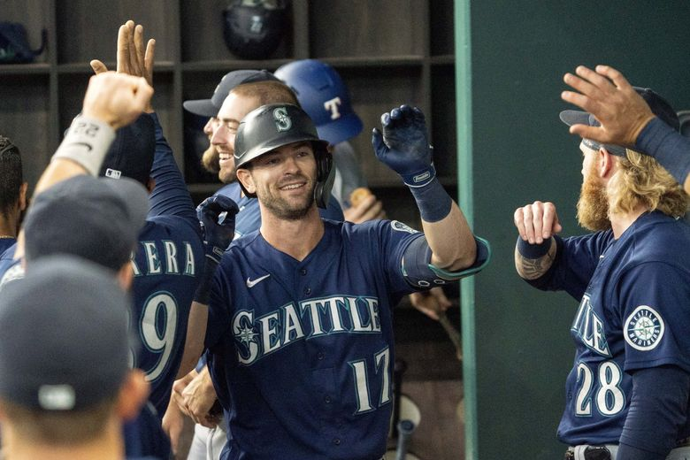 Seattle Mariners' Mitch Haniger is congratulated in the dugout after hitting a three run home run against the Texas Rangers that scored Jake Bauers and J.P. Crawford during the second inning of a baseball game Thursday, Aug. 19, 2021, in Arlington, Texas.  (Jeffrey McWhorter / The Associated Press)