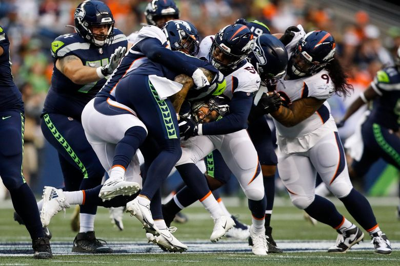 Seahawks quarterback Alex McGough is sacked by the Denver Broncos defense during the first quarter of a preseason game Saturday. (Jennifer Buchanan / The Seattle Times)