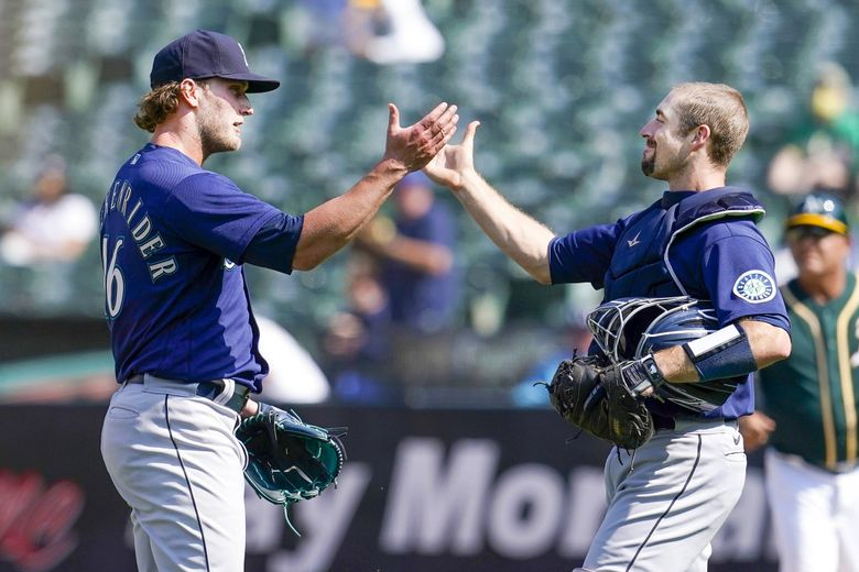 Seattle Mariners pitcher Drew Steckenrider, left, celebrates with catcher Tom Murphy after the Mariners defeated the Oakland Athletics in Oakland, Calif., Tuesday, Aug. 24, 2021. (Jeff Chiu / The Associated Press)