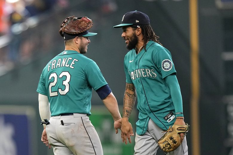 Seattle Mariners' Ty France and J.P. Crawford celebrate after a 6-3 win in 11 innings against the Astros, Aug. 22, 2021, in Houston. (David J. Phillip / The Associated Press)