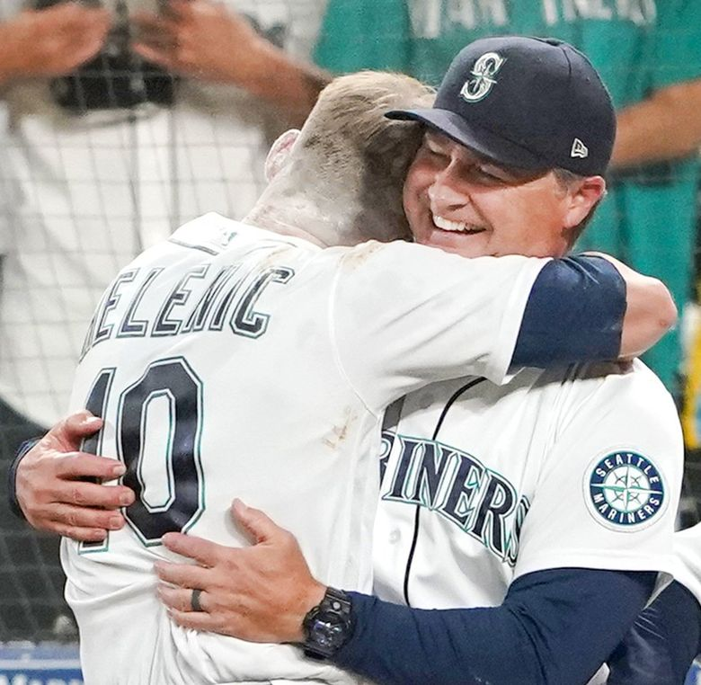 The Mariners' Jarred Kelenic hugs manager Scott Servais after Kelenic scored the winning run on a wild pitch during the ninth inning against the Athletics last month. (Ted S. Warren / AP)