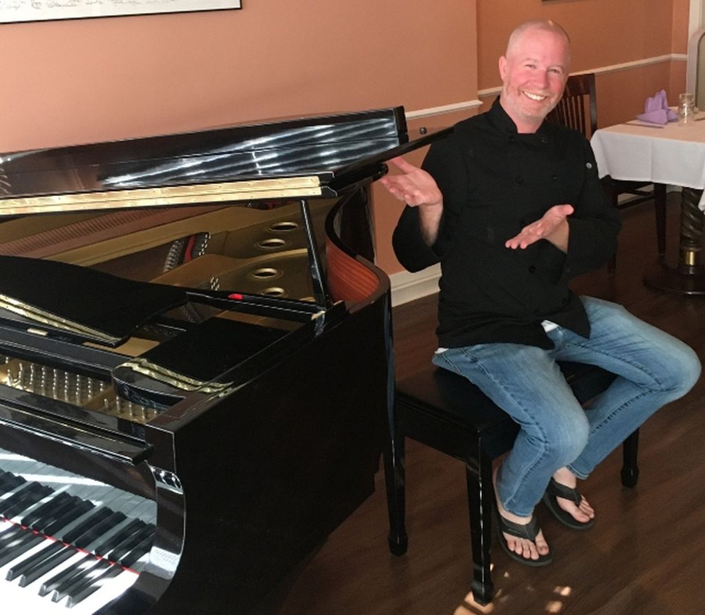 Jason Moore, former manager of Tula's jazz club, shows off the new baby grand piano at Calluna, the restaurant he opened in Ravenna that is now booking jazz acts. (Paul de Barros)