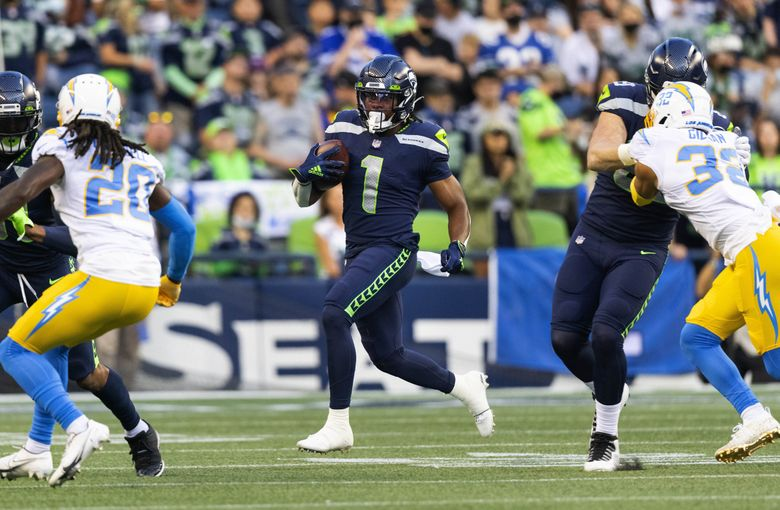 Dee Eskridge takes the handoff for his first touch in a Seahawks uniform Saturday night. (Dean Rutz / The Seattle Times)