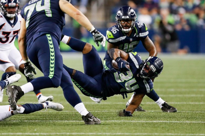 Seattle Seahawks running back Josh Johnson is upended during a preseason game against the Denver Broncos, Aug. 21, 2021, in Seattle. (Jennifer Buchanan / The Seattle Times)