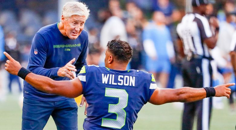 Seattle Seahawks head coach Pete Carroll chats with quarterback Russell Wilson before the start of a preseason game against the Los Angeles Chargers, Aug. 28, 2021, in Seattle. (Jennifer Buchanan / The Seattle Times)