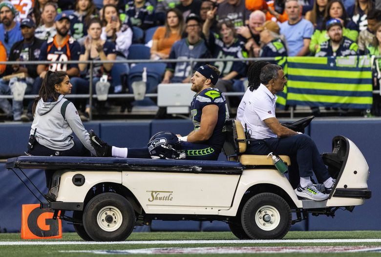 Seahawks linebacker Ben Burr-Kirven is taken off the field by cart after being injured on the opening kickoff against the Denver Broncos in a preseason game Aug. 21, 2021 in Seattle. (Dean Rutz / The Seattle Times)