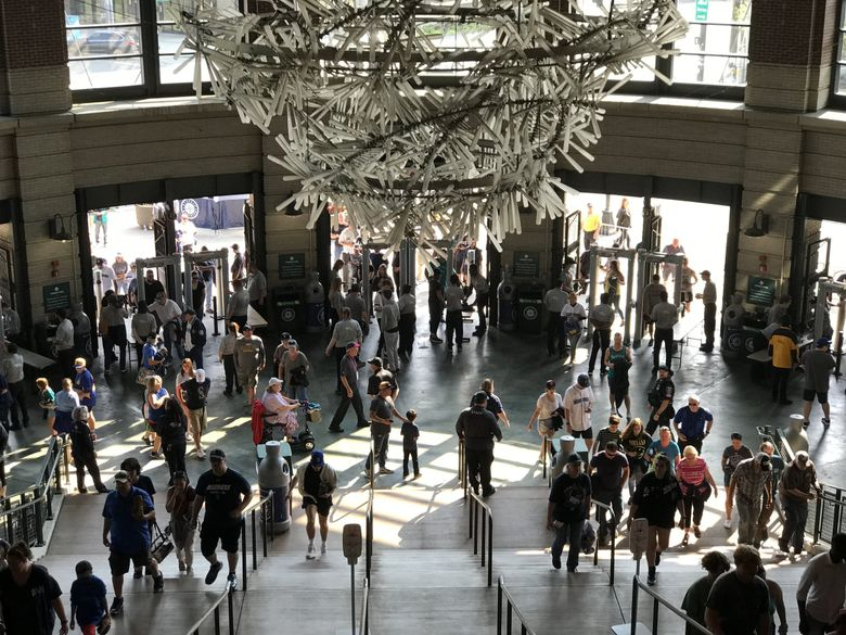 Fans enter T-Mobile Park on July 2, the Mariners' first home game after the lifting of most coronavirus restrictions in Washington. An indoor mask mandate has since been reinstated.  (Dean Rutz / The Seattle Times)