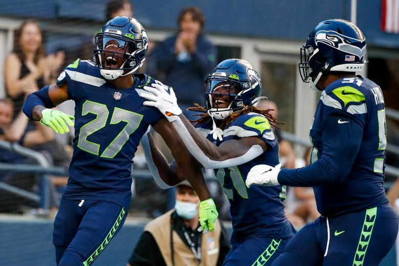 Seattle Seahawks defensive back Marquise Blair (left) celebrates with cornerback Tre Flowers and defensive end Kerry Hyder after scoring a touchdown on a turnover during the first quarter of a game against the Los Angeles Chargers Saturday, Aug. 28, 2021, in Seattle. (Jennifer Buchanan / The Seattle Times)