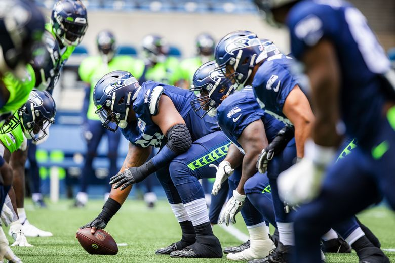 Center Kyle Fuller, guard Damien Lewis and tackle Stone Forsythe take their places on the offensive line for warmups before before the Seahawks play a mock game as part of training camp at Lumen Field in Seattle Sunday, Aug. 8, 2021.  (Bettina Hansen / The Seattle Times)