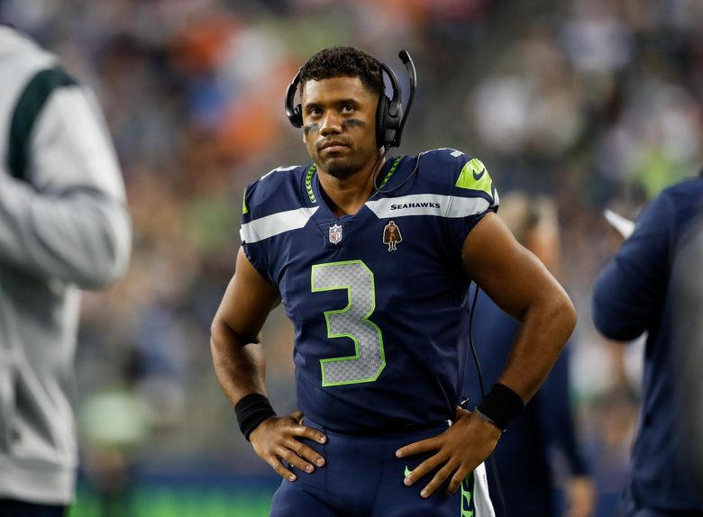 Seahawks quarterback Russell Wilson looks on from the sidelines during the second quarter of a preseason game against the Denver Broncos on Saturday. (Jennifer Buchanan / The Seattle Times)